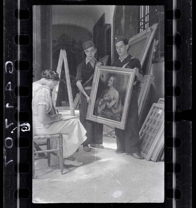 "SPAIN. Madrid. October/November, 1936. Woman making an inventory of the paintings in the collection of Las Descalzas Reales with two Republican soldiers. (Negative from the ""Mexican Suitcase."")   Contact email: New York : photography@magnumphotos.com Paris : magnum@magnumphotos.fr London : magnum@magnumphotos.co.uk Tokyo : tokyo@magnumphotos.co.jp  Contact phones: New York : +1 212 929 6000 Paris: + 33 1 53 42 50 00 London: + 44 20 7490 1771 Tokyo: + 81 3 3219 0771  Image URL: http://www.magnumphotos.com/Archive/C.aspx?VP3=ViewBox_VPage&IID=2K7O3RTQQEEW&CT=Image&IT=ZoomImage01_VForm"