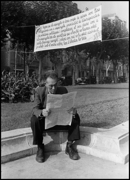 SPAIN. Barcelona. October- November 1936. The Spanish Civil War. Man reading under an anti-fascist banner.