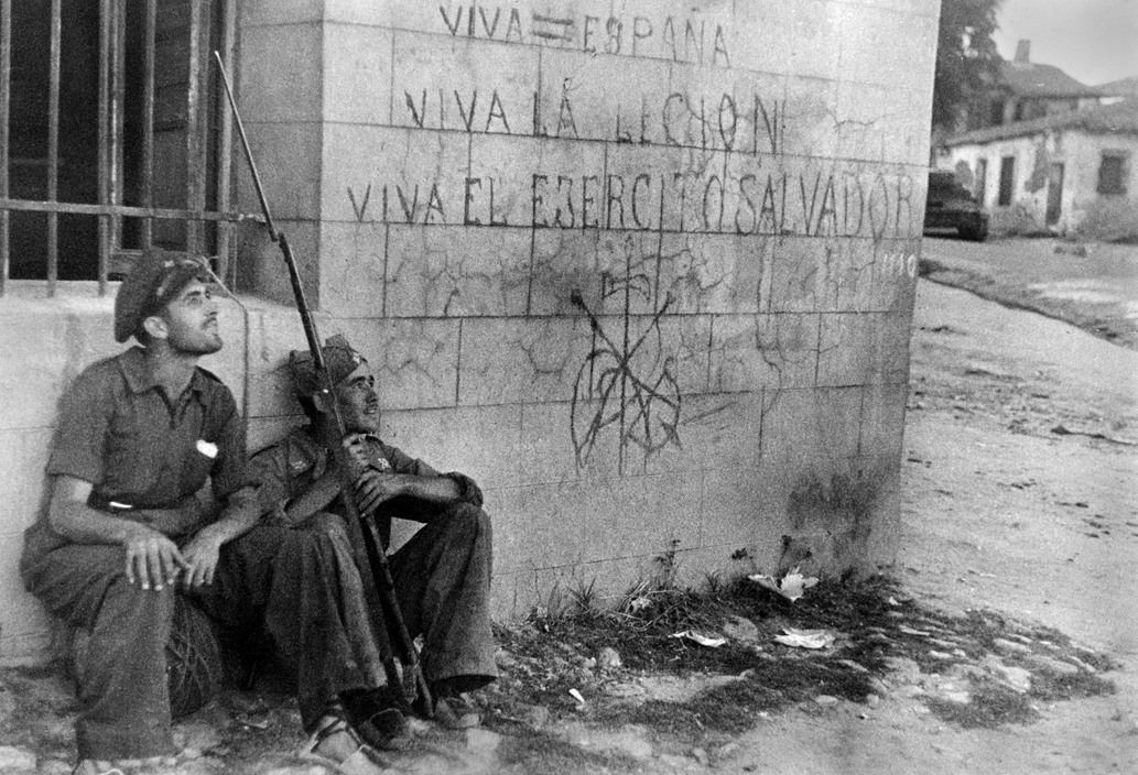 Two Republican soldiers in front of wall with rightist slogans and symbols, Battle of Brunete, Spain, July 1937
