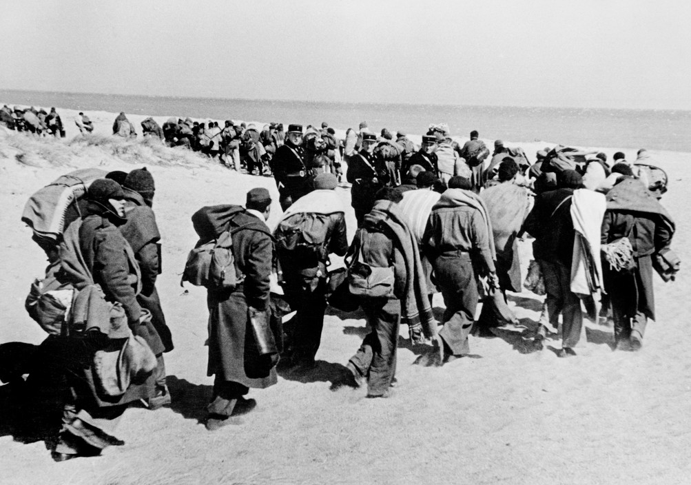 FRANCE. March 1939. Between Argeles-sur-Mer and Le Bercares. Exiled Republican soldiers and civilians, who crossed the border after Franco's victory, being transferred from one refugee camp to another. A French Gendarme heads the column of refugees. France had set up eight camps along the border in the PyrŽnŽes Orientales region.