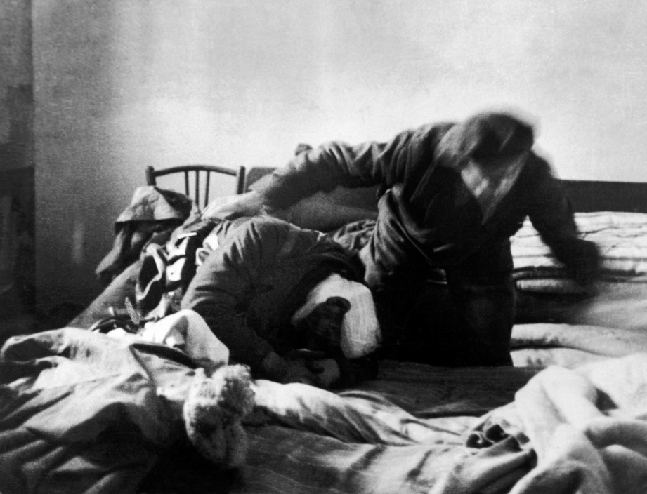 SPAIN. Spanish Civil War (1936-9).  Madrid. November/December, 1936. Members of the International Brigades, by a slaughterhouse, near the university campus, in the western outskirts of the capital. One of them is helping a wounded comrade. The Fascist rebels were mounting a major offense in order to capture Madrid.  The Spanish Civil War broke out in 1936, when part of the Spanish army rebelled against the Second Republic, a democratic government elected in 1931. It gained international dimensions when Fascist Germany and Italy began supporting the military uprising, led by General Franco, with weapons and soldiers. The USSR helped the Republic, and a significant contingent of volunteers joined the International Brigades and fought for the Republic. The conflict became the symbol of a larger conflict between Fascists and Communists. The war ended in 1939 with Franco's victory over the Republicans.