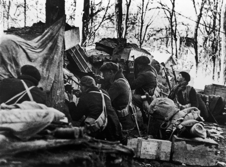 SPAIN. Spanish Civil War (1936-9).  Madrid. November/December, 1936. Members of the International Brigades defending a barricade by a slaughterhouse, near the university campus, in the western outskirts of the capital. The Fascist rebels were mounting a major offense in order to capture Madrid.    The Spanish Civil War broke out in 1936, when part of the Spanish army rebelled against the Second Republic, a democratic government elected in 1931. It gained international dimensions when Fascist Germany and Italy began supporting the military uprising, led by General Franco, with weapons and soldiers. The USSR helped the Republic, and a significant contingent of volunteers joined the International Brigades and fought for the Republic. The conflict became the symbol of a larger conflict between Fascists and Communists. The war ended in 1939 with Franco's victory over the Republicans.