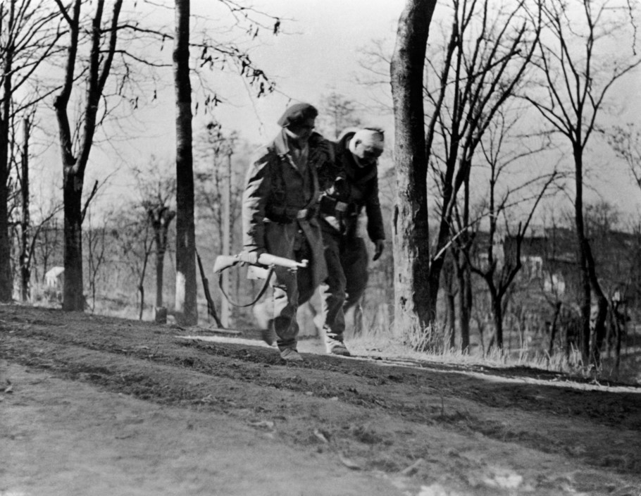 SPAIN. Spanish Civil War (1936-9).  Madrid. November/December, 1936. Members of the International Brigades by a slaghterhouse, near the university campus, in the Western outskirts of the capital. A member of the Brigade is helping a wounded comrade. The Fascist rebels were mounting a major offense in order to capture Madrid.  The Spanish Civil War broke out in 1936, when part of the Spanish army rebelled against the Second Republic, a democratic government elected in 1931. It gained international dimensions when Fascist Germany and Italy began supporting the military uprising, led by General Franco, with weapons and soldiers. The USSR helped the Republic, and a significant contingent of volunteers joined the International Brigades and fought for the Republic. The conflict became the symbol of a larger conflict between Fascists and Communists. The war ended in 1939 with Franco's victory over the Republicans.