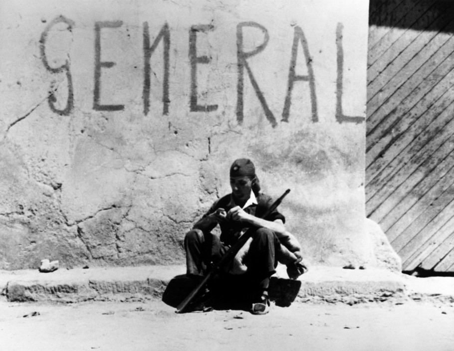 SPAIN. Spanish Civil War (1936-9)  Aragon front. August/September, 1936. Republican soldier outside the local General Headquarters.    The Spanish Civil War broke out in 1936, when part of the Spanish army rebelled against the Second Republic, a democratic government elected in 1931. It gained international dimensions when Fascist Germany and Italy began supporting the military uprising, led by General Franco, with weapons and soldiers. The USSR helped the Republic, and a significant contingent of volunteers joined the International Brigades and fought for the Republic. The conflict became the symbol of a larger conflict between Fascists and Communists. The war ended in 1939 with Franco's victory over the Republicans.